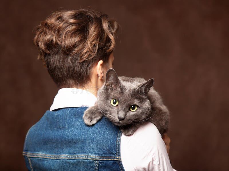 有蓝色俄国猫的美丽的少妇 对宠物的爱 Studi 免版税库存照片