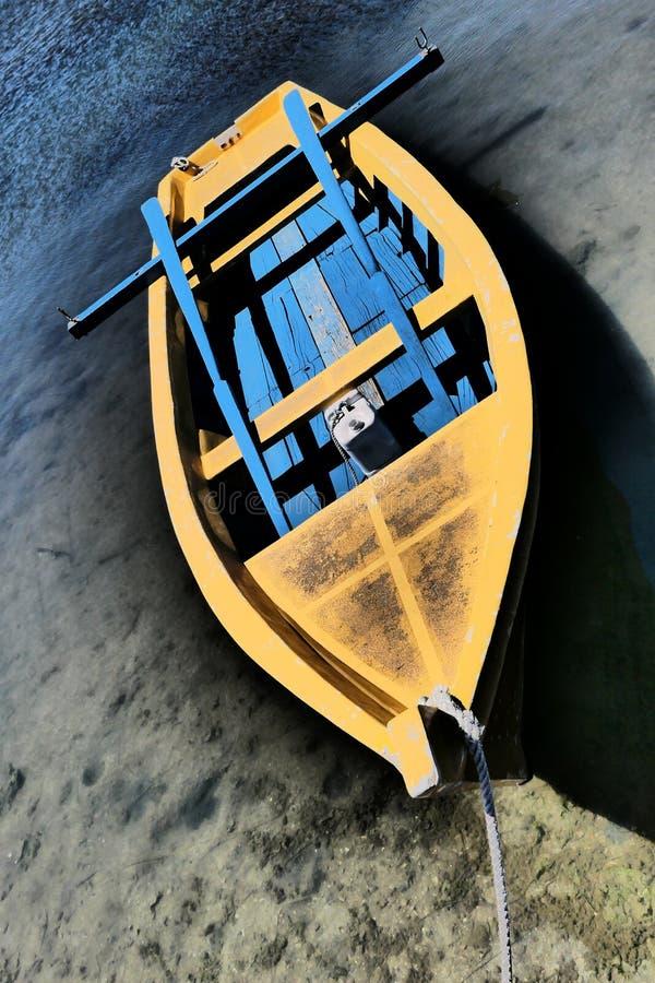 有蓝色内部、桨和垂直的木桨支持的有一点退色的黄色渔船 免版税库存图片