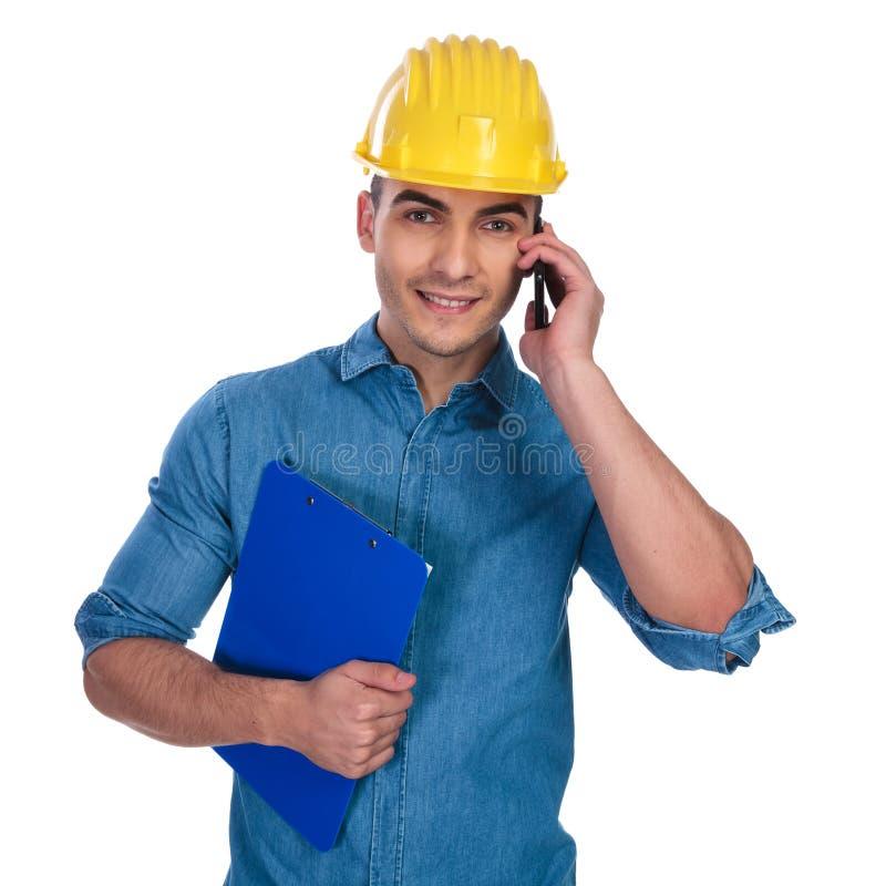 有蓝色剪贴板的年轻学生在电话里说 库存照片