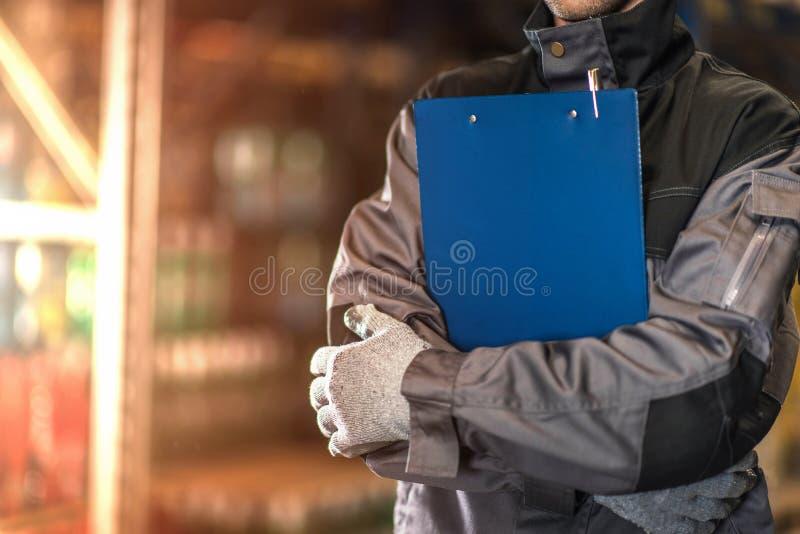 有蓝色剪贴板特写镜头照片的仓库工作者 图库摄影