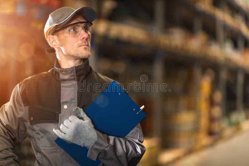有蓝色剪贴板的仓库工作者 库存图片