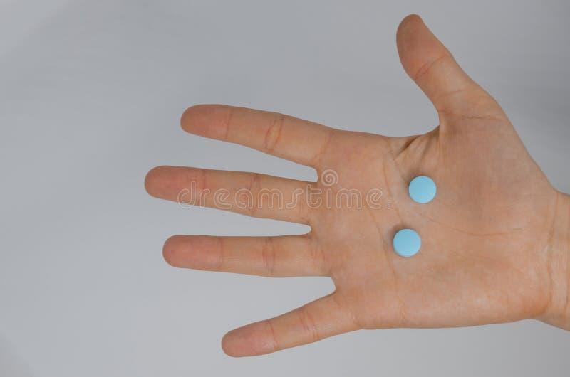 有蓝色医疗药片的一只手 免版税库存照片
