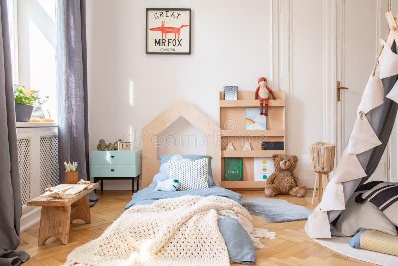 有蓝色卧具的舒适孩子卧室和在床上的温暖的毯子,与大模型海报的真正的照片在地板上 免版税库存图片