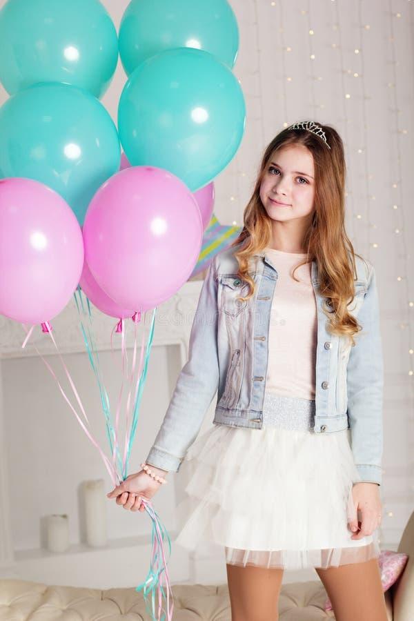 有蓝色和桃红色气球的甜少年女孩 免版税库存图片