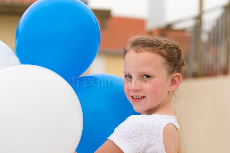 有蓝色和白色气球的愉快的女孩 免版税库存照片