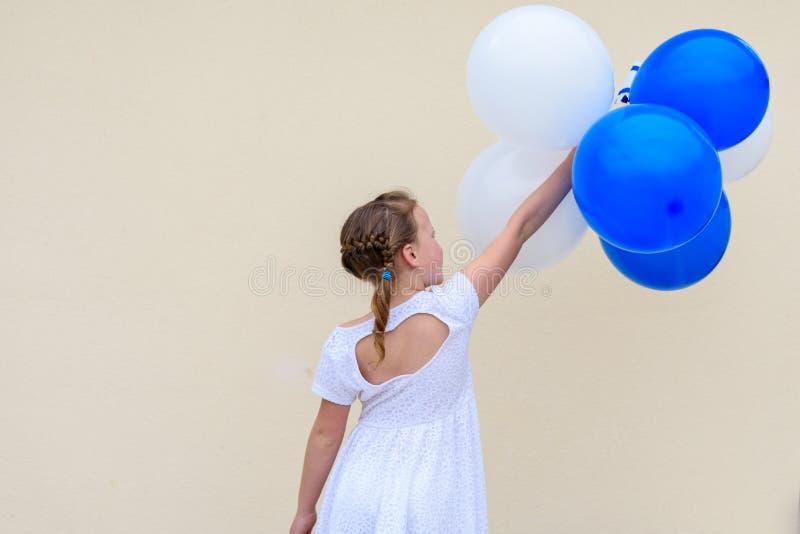 有蓝色和白色气球的愉快的女孩 免版税库存图片