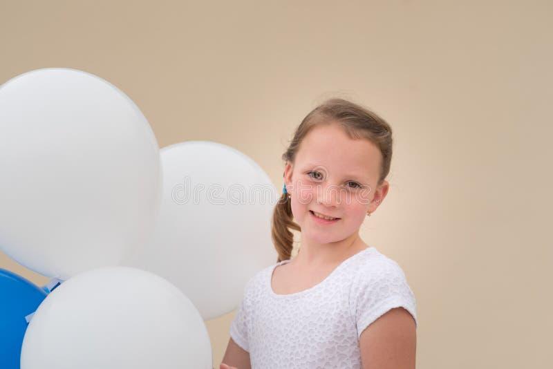 有蓝色和白色气球的愉快的女孩 免版税图库摄影