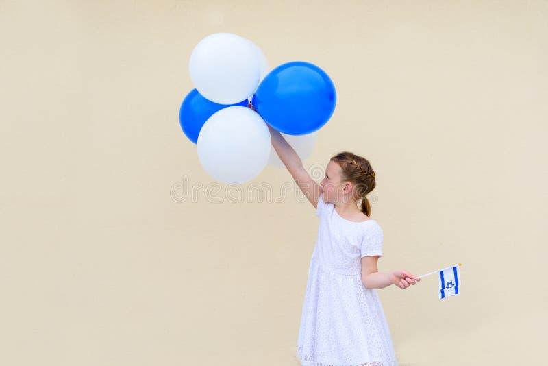 有蓝色和白色气球ans以色列旗子的愉快的女孩 库存图片
