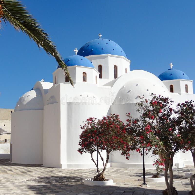 有蓝色圆顶的白色教会在深蓝天下在Perrisa,圣托里尼,希腊 库存图片