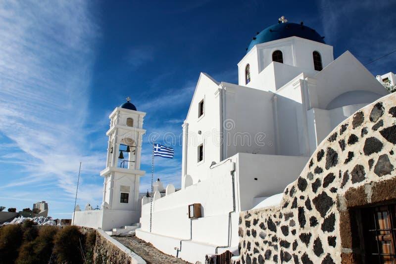 有蓝色圆顶的美丽的白色教会和在海岛上的希腊旗子 免版税库存图片