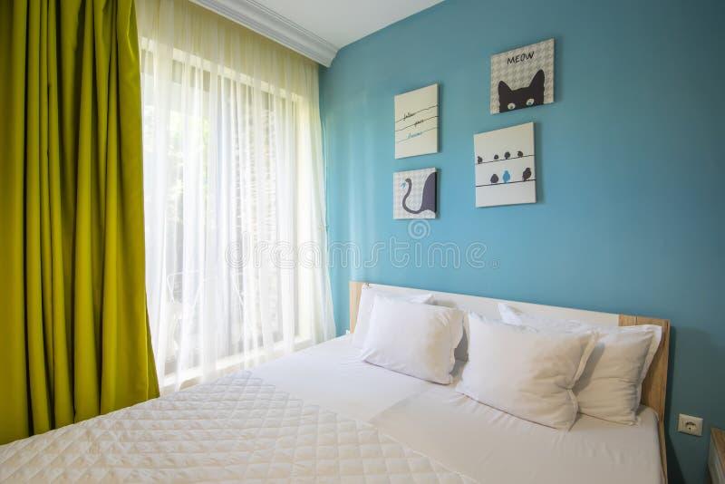 有蓝色墙壁、白色剪、枕头套和板料的旅馆卧室 绿色帷幕 免版税库存照片