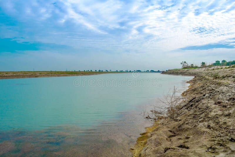 有蓝色多云天空的蓝色美丽的湖 图库摄影