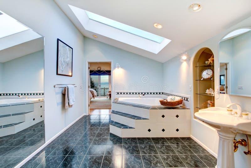 有蓝色大理石砖地和角落浴盆的主要卫生间 免版税库存照片