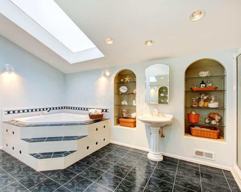 有蓝色大理石砖地和角落浴盆的主要卫生间 免版税图库摄影