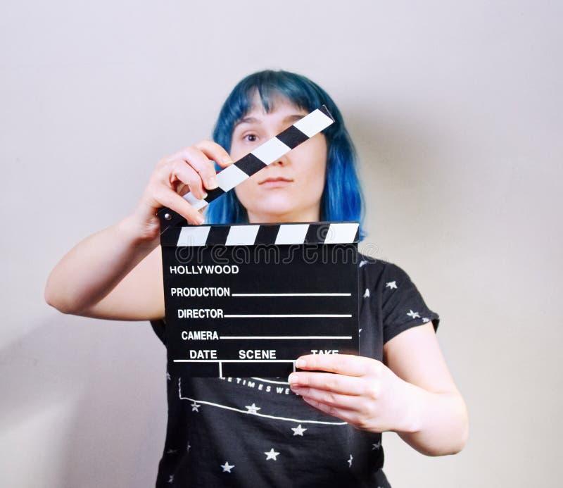 有蓝色头发的一个女孩,拿着拍板 免版税库存图片
