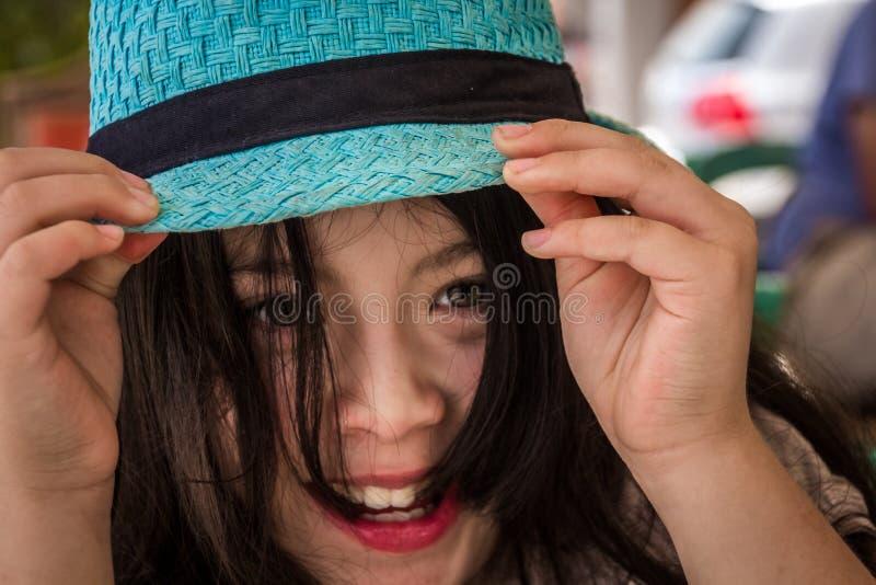 有蓝色帽子的微笑的青少年的女孩 免版税库存照片