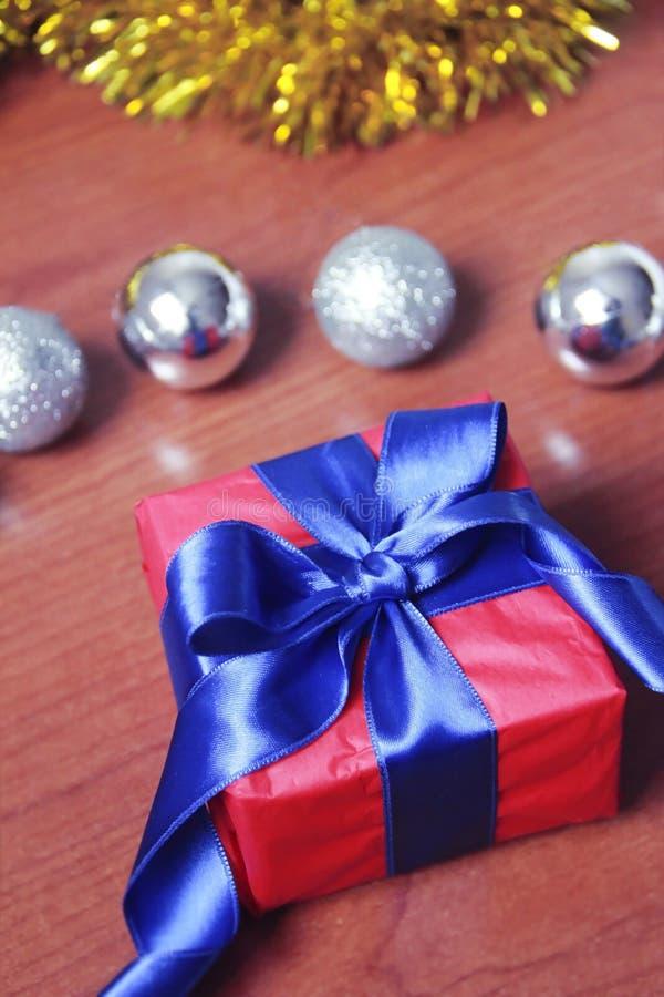 有蓝色弓的红色礼物盒在圣诞节玩具背景为新年假日 库存图片