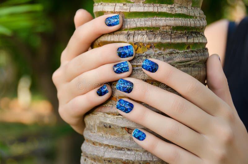 有蓝色指甲艺术贴纸的女性手 免版税库存照片
