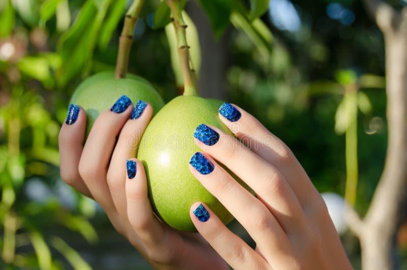 有蓝色指甲艺术贴纸的女性手 图库摄影