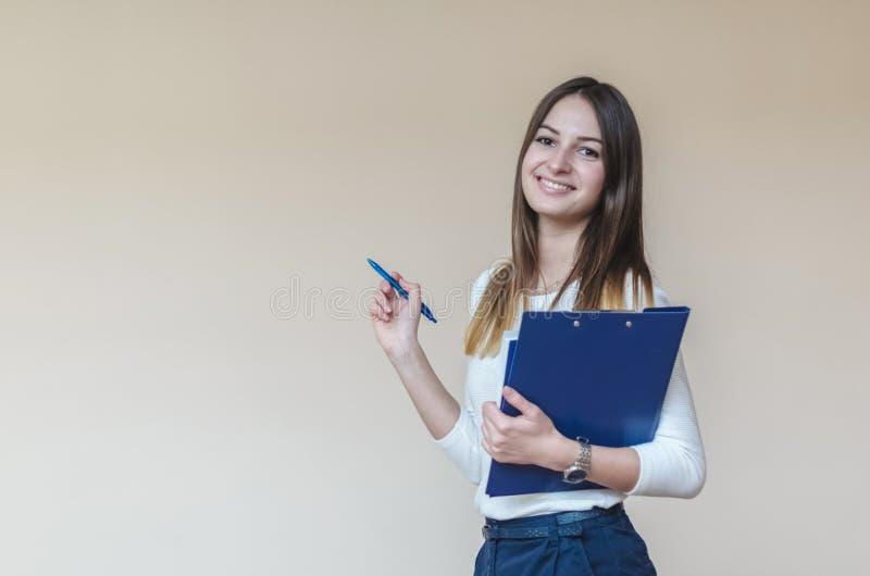 有蓝色文件夹的年轻深色的在轻的背景的女孩和笔 免版税库存图片