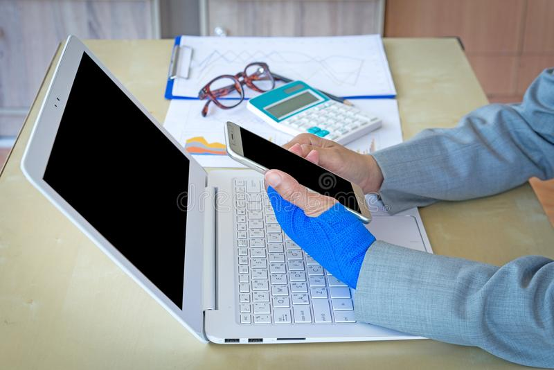 有蓝色有弹性绷带的受伤的妇女在手边和举行响度单位 免版税库存照片