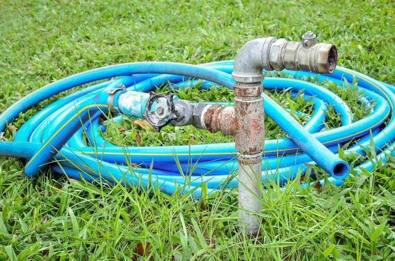 有蓝色橡胶水水管的老水阀门 免版税库存照片