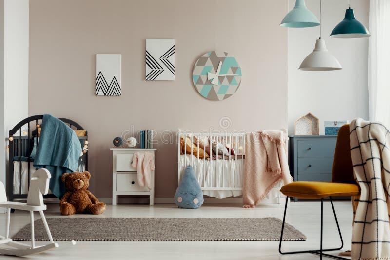 有蓝色毯子的灰色小儿床在优等的婴孩卧室的角落 库存图片