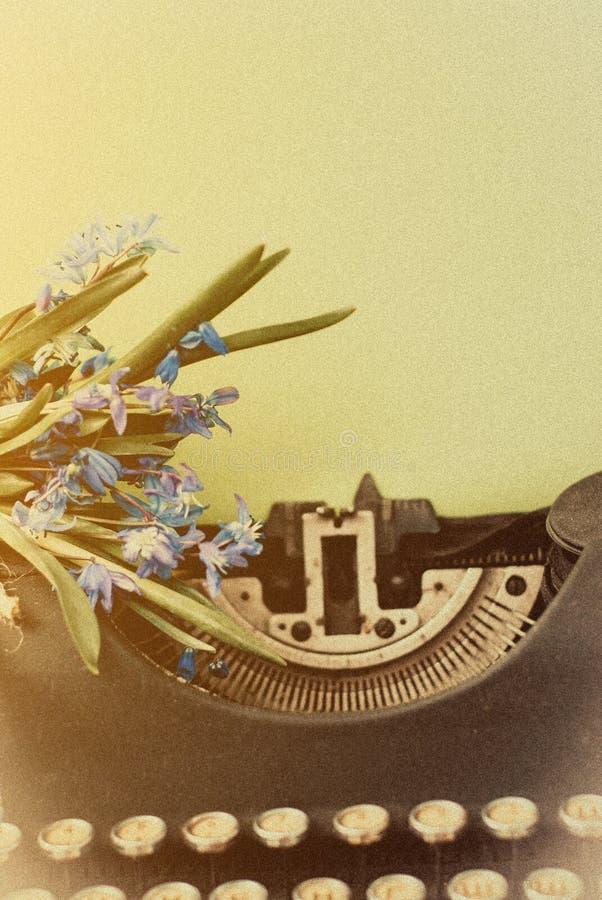 有蓝色浪漫春天的老古色古香的黑葡萄酒打字机开花 库存图片