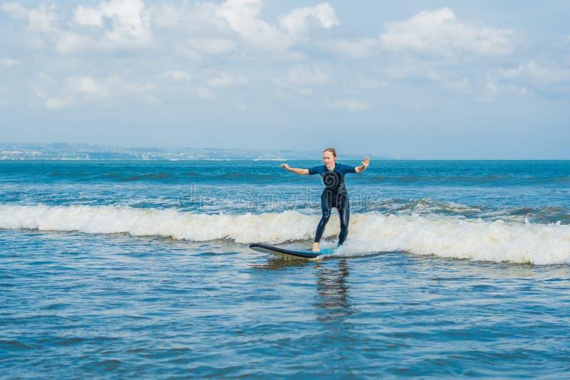 有蓝色海浪的快乐的年轻女人初学者冲浪者获得在小海波浪的乐趣 活跃家庭生活方式,室外的人们 免版税库存照片