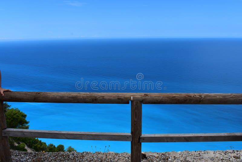 有蓝色海的木篱芭在背景中 免版税库存照片