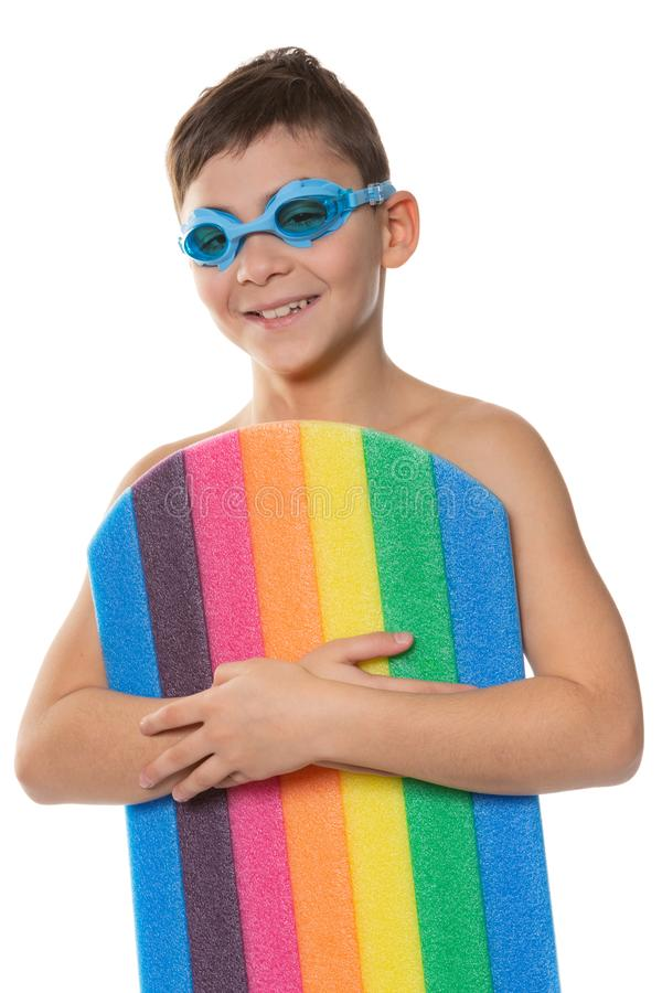 有蓝色游泳的风镜的愉快的男孩和游泳的体育的板、概念和休闲,在白色背景 免版税库存照片