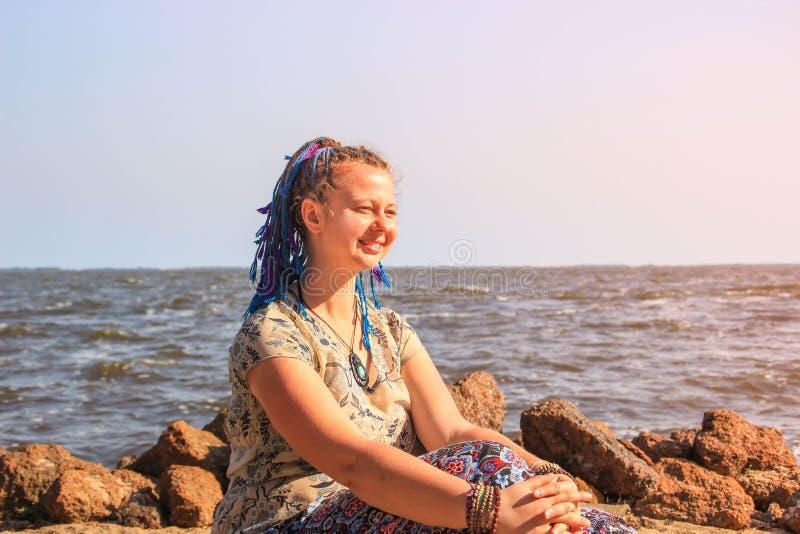 有蓝色猪尾头发的一个肥满年轻白女孩旅客赤足坐沙子反对维多利亚湖背景  免版税图库摄影