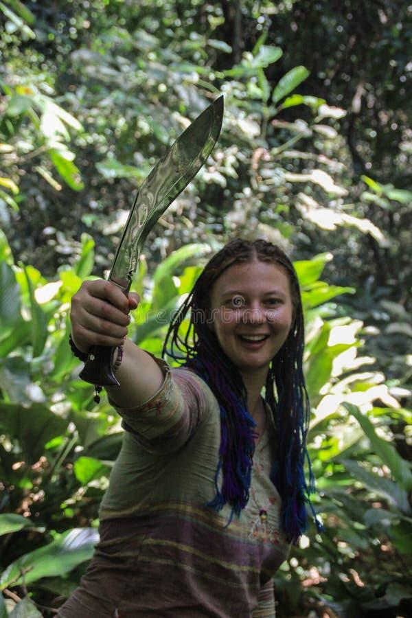 有蓝色猪尾头发的年轻白女孩旅客在拿着大砍刀的密林 免版税库存图片