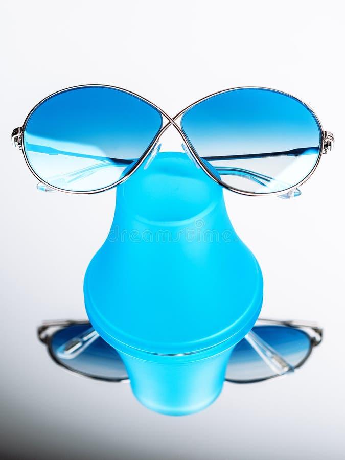 有蓝色玻璃的太阳镜在一个蓝色立场 图库摄影