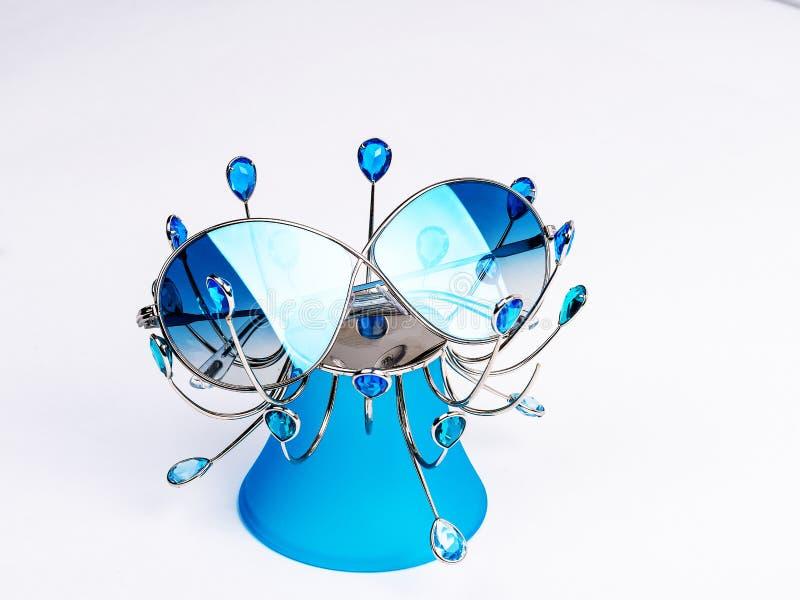 有蓝色玻璃的太阳镜在一个蓝色立场 库存图片