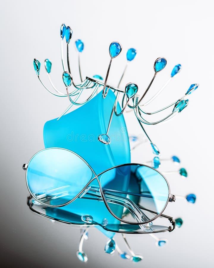 有蓝色玻璃的太阳镜在与一个金属立场的构成在镜子 免版税库存图片