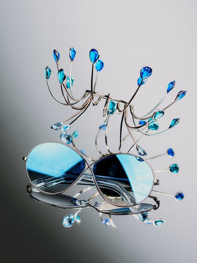 有蓝色玻璃的太阳镜在与一个金属立场的构成在镜子 库存照片