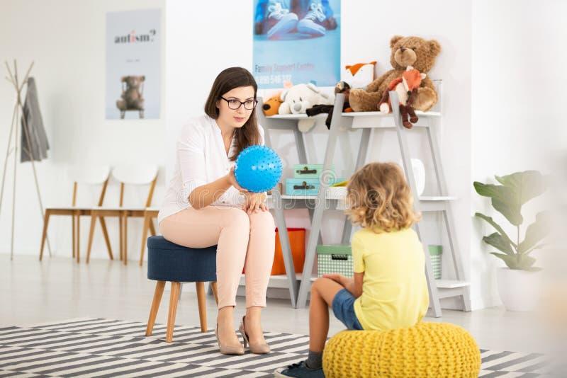 有蓝色球的老师和亲切的孩子在有玩具的教室 图库摄影