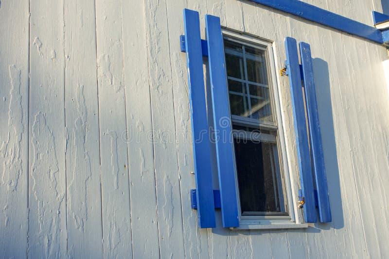 有蓝色百叶窗的白色和蓝色木家与日出su 图库摄影