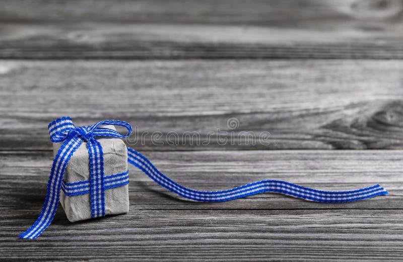 有蓝色的礼物盒检查了在木灰色背景的丝带 库存照片