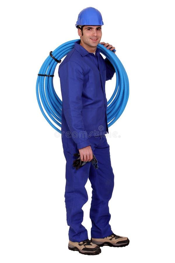 有蓝色管子的水管工 免版税库存照片