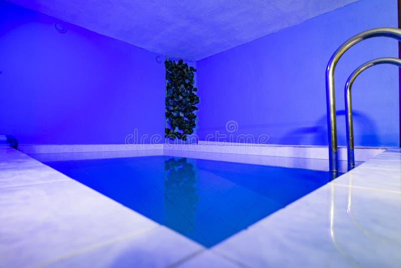 有蓝色色的照明设备的内部小游泳场 库存照片