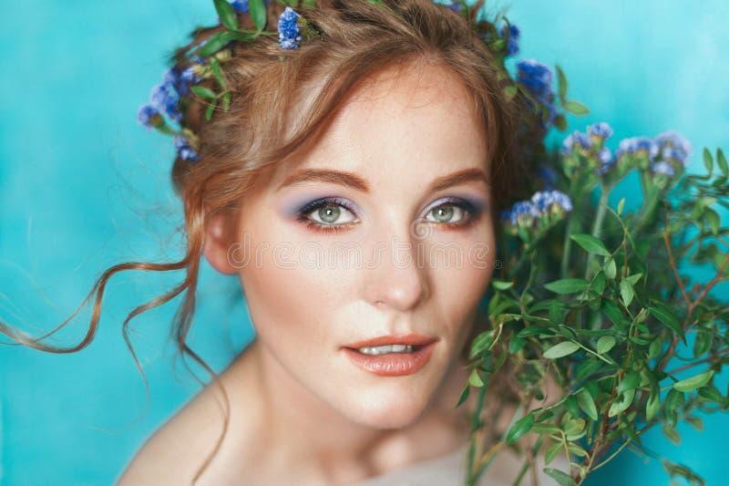 有蓝色花的女孩在浅兰的背景 春天美景画象 免版税库存图片