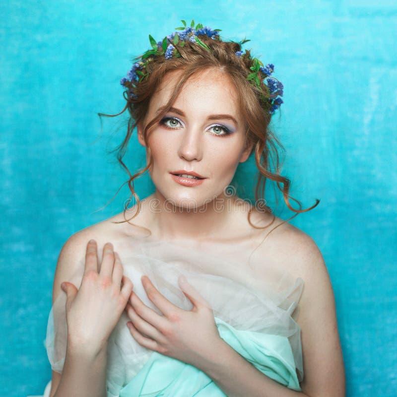 有蓝色花的年轻人微笑的嫩女孩在浅兰的背景 春天美景画象 免版税库存图片