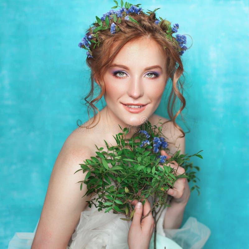 有蓝色花的年轻人微笑的嫩妇女在浅兰的背景 春天美景画象 免版税库存照片