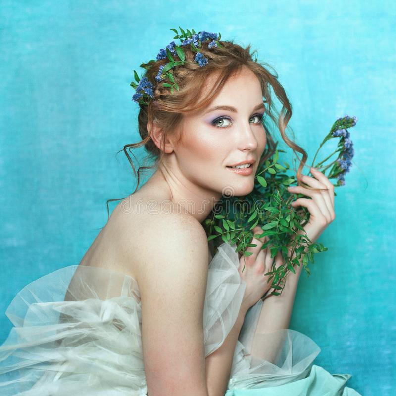 有蓝色花的年轻微笑的女孩在浅兰的背景 春天美景画象 免版税图库摄影