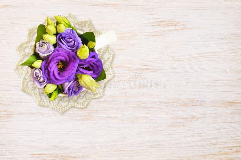 有蓝色花的杯和在木头的钩针编织小垫布 免版税库存照片