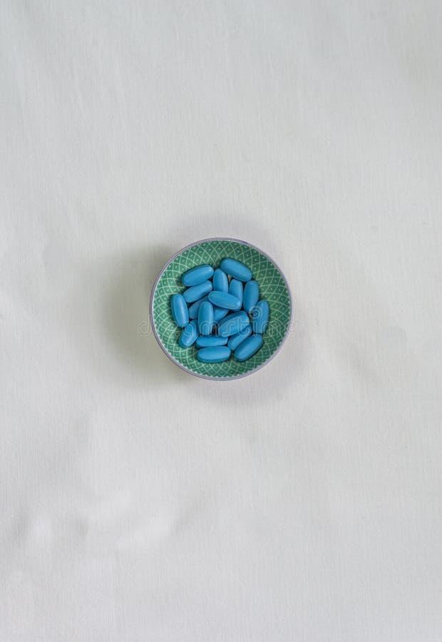 有蓝色药片的小碗 库存照片