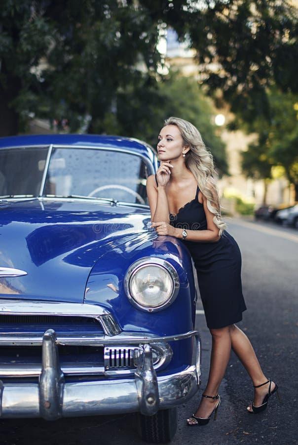 有蓝色葡萄酒汽车的美丽的白肤金发的典雅的女孩 图库摄影