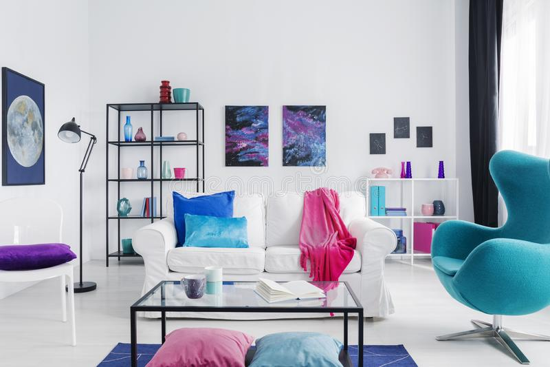 有蓝色蛋椅子的折衷客厅,金属咖啡桌和白色长沙发有五颜六色的枕头的,真正的照片与拷贝空间 库存图片